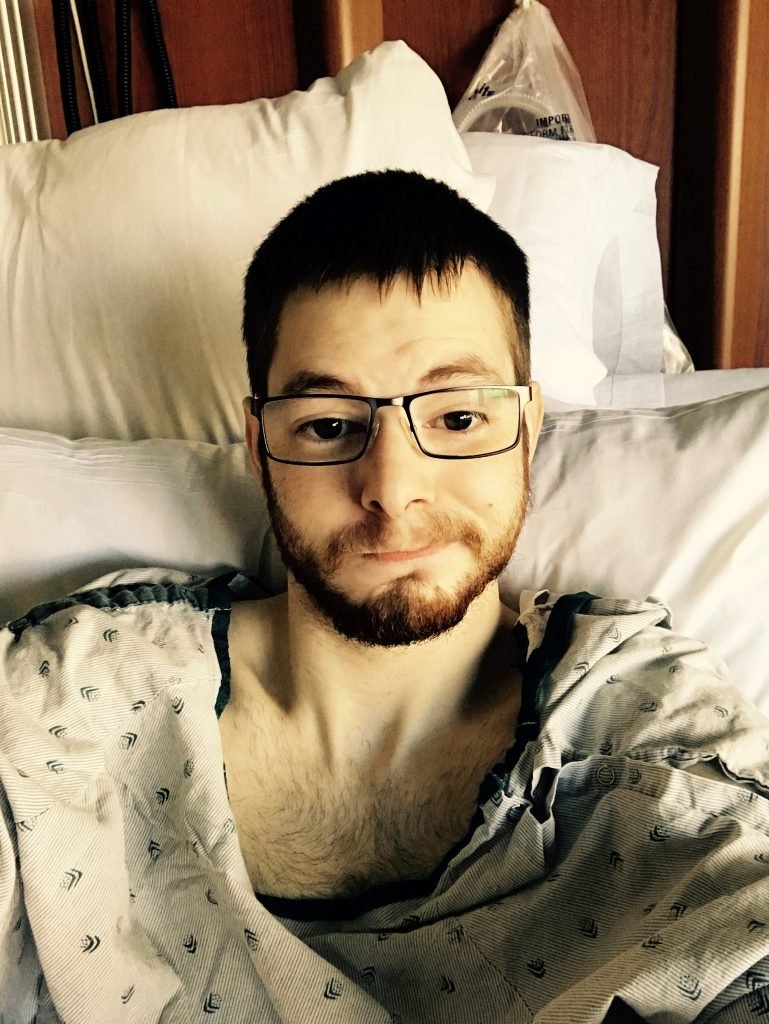 Young man in hospital bed after donating bone marrow.