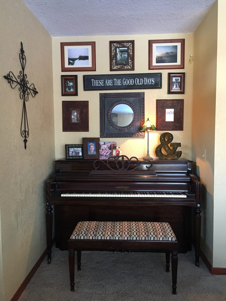 Living room with cross, piano, and family photos.